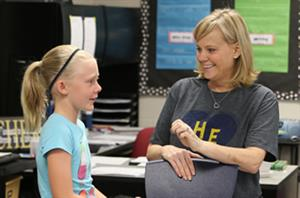 Photo of teacher visiting with student.
