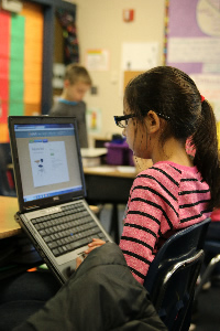 Photo of student using a laptop in classroom
