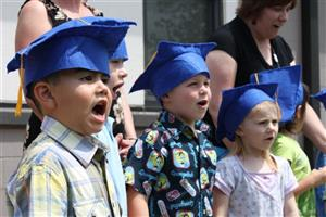 Photo of Early Childhood students signing during a graduation program.