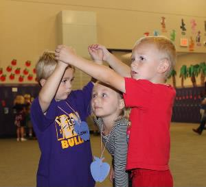 Photo of three early childhood students participating in an activity.