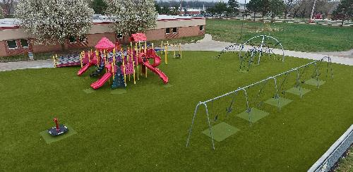 Photograph of example playground renovation with modern surface and equipment.
