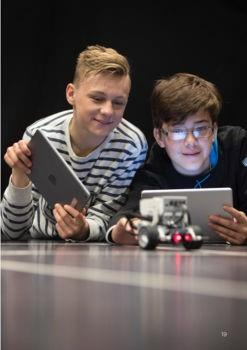 Two students using iPads to code and control a robotic device.