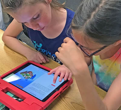 Image of two students interacting with an iPad in class.