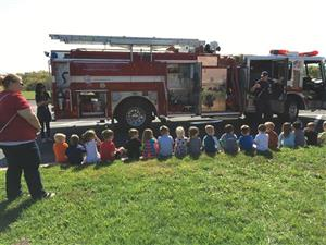 Photo of students learning from firefighters about fire safety